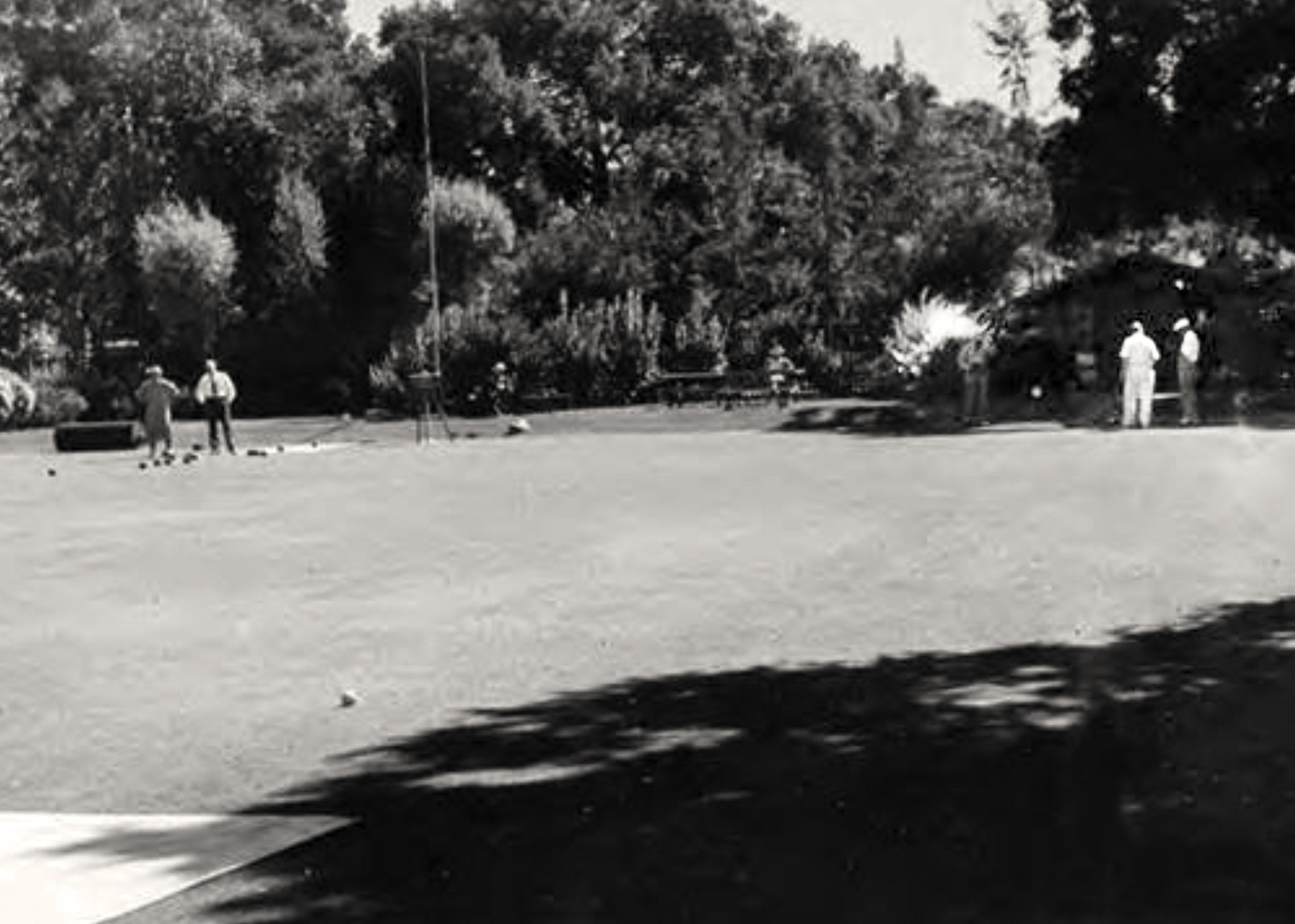 The green about 1936 looking towards where the clubhouse stands today. The old flagpole is just visible in front of the trees to the left of the figure seated center left. The original shed is behind the two bowlers to the right. Note the sloping bank behind the green. There also appears to be a roller on the green to the left. PAHA photo.