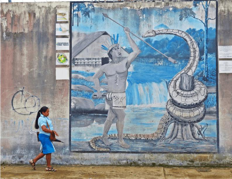 The streets of Mitú: a local woman passes a mural of an Indigenous man doing battle with a giant anaconda. Snakes are an important part of local Indigenous cosmology and there are several murals and statues featuring snakes around Mitú