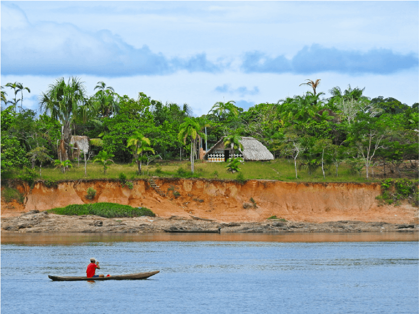A local fisherman on the Vaupés River with an Indigenous Maloca in the background: this photo was taken from Mitú