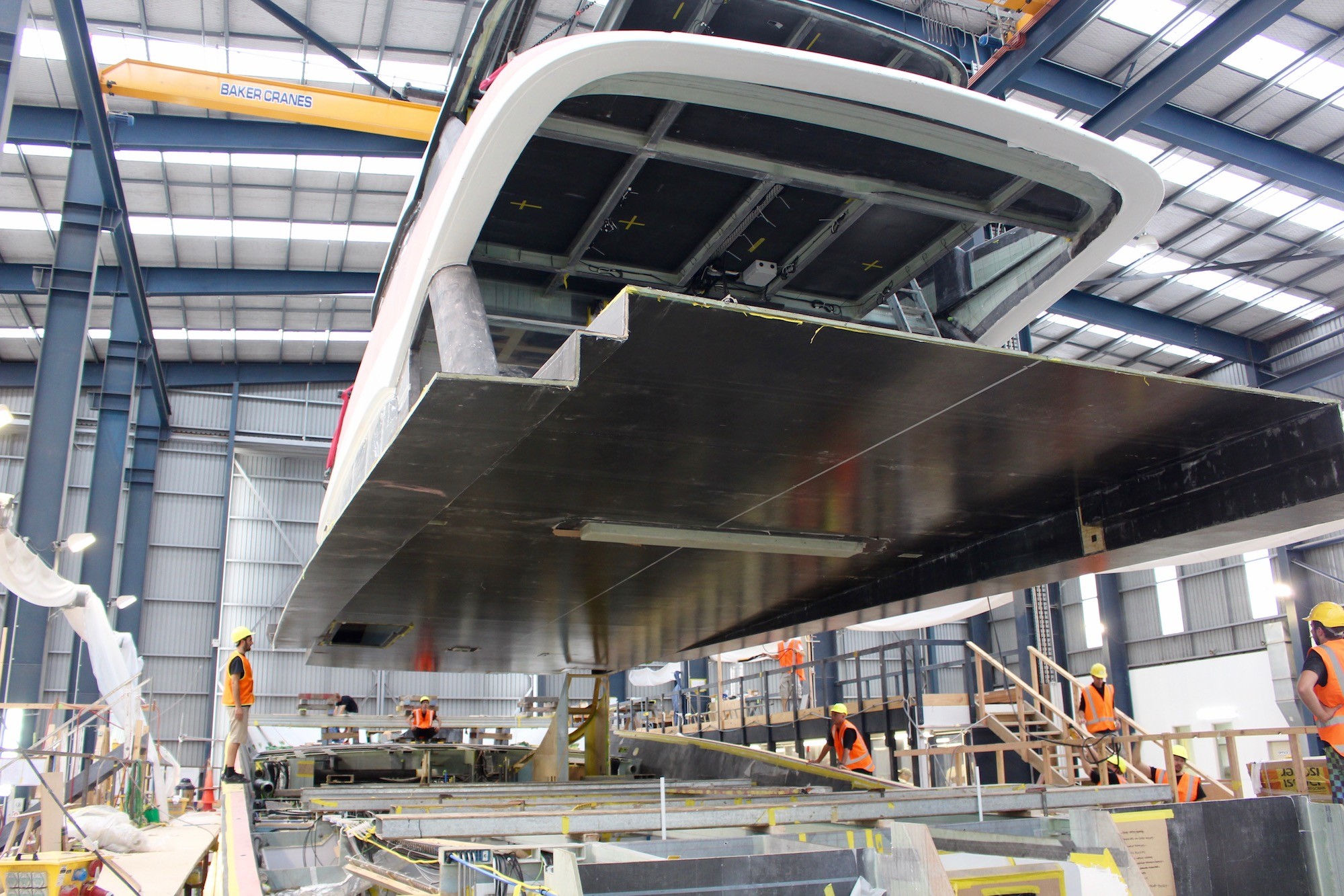 Hull 1015 superstructure enters the shed and is lifted on to the hull – image Paige Cook