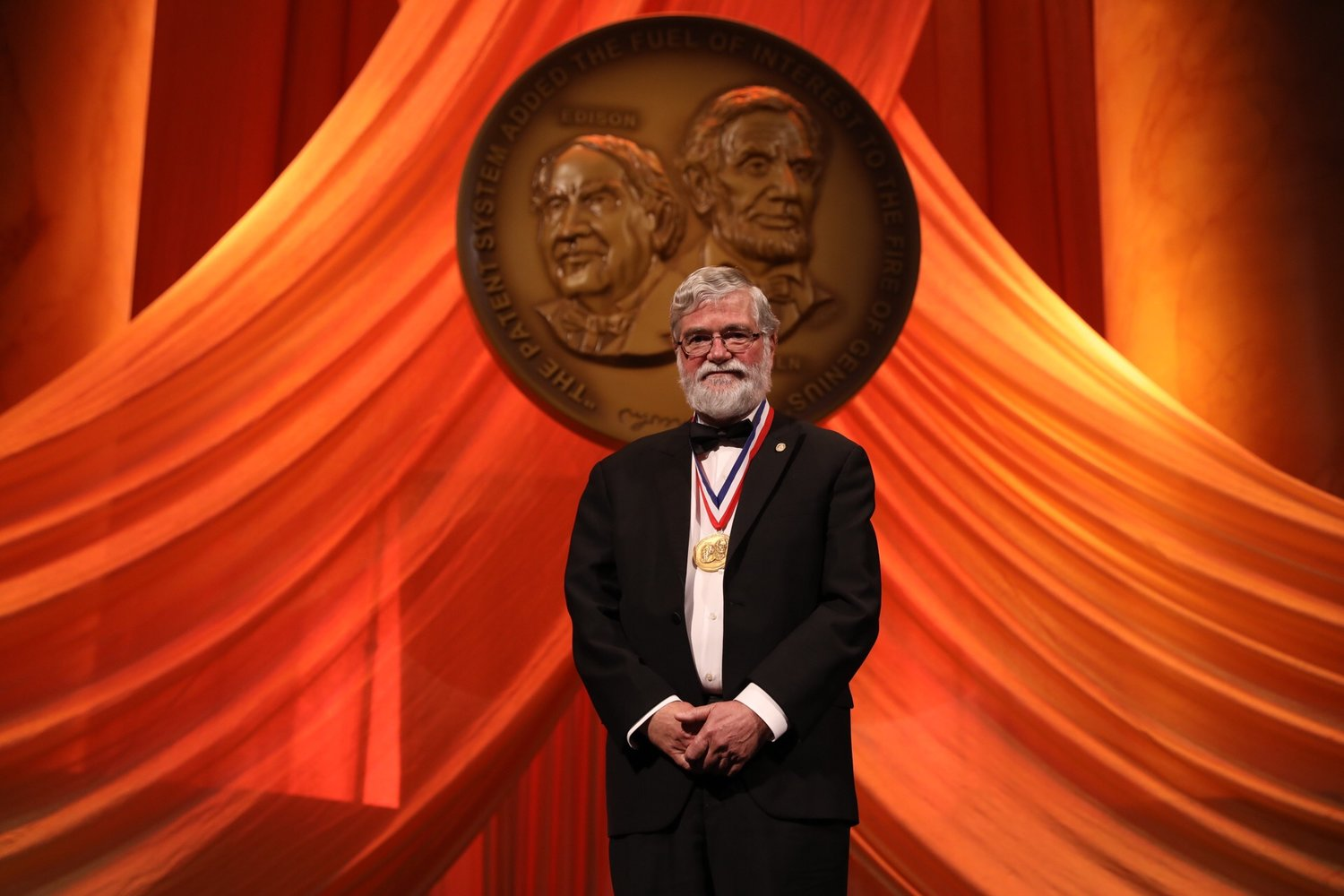 """Don Arney, newly inducted into the 2017 National Inventors Hall of Fame, stands under the medal, with Edison and Lincoln looking on. The inscription reads: """" The Patent System Added The Fuel Of Interest To The Fire Of Genius. """""""
