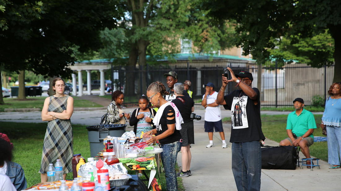 Event attendees and community members look on as the poets perform, and partake in the picnic refreshments provided.