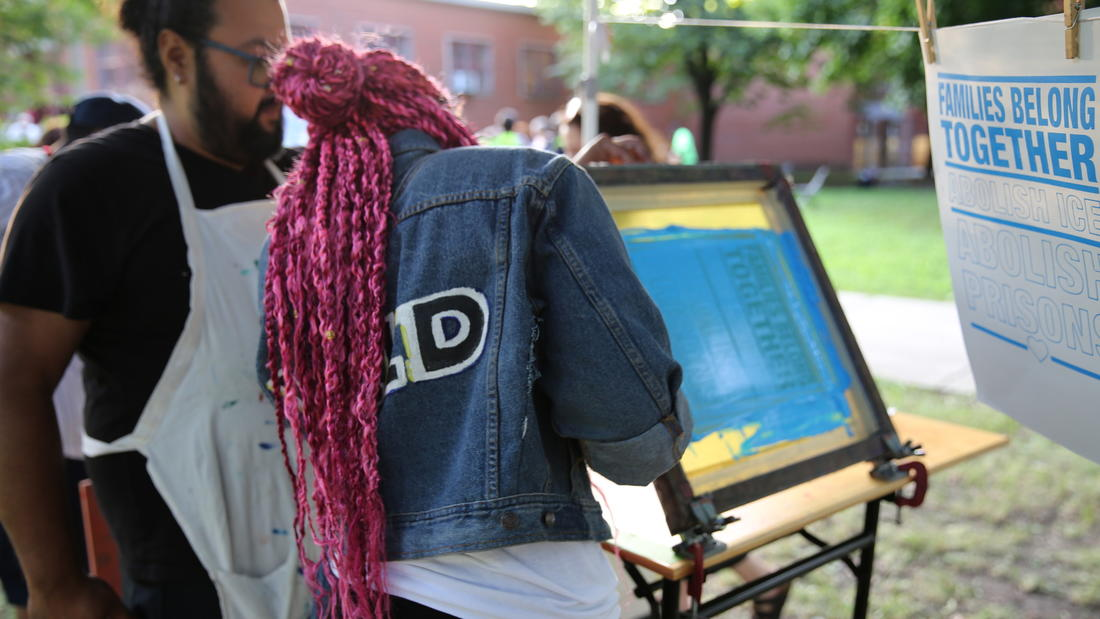 Multidisciplinary artist William Estrada teaches an event attendee how to screen print at his Mobile Street Art Cart project. The cart brings free, culturally relevant art workshops into Chicago neighborhoods.
