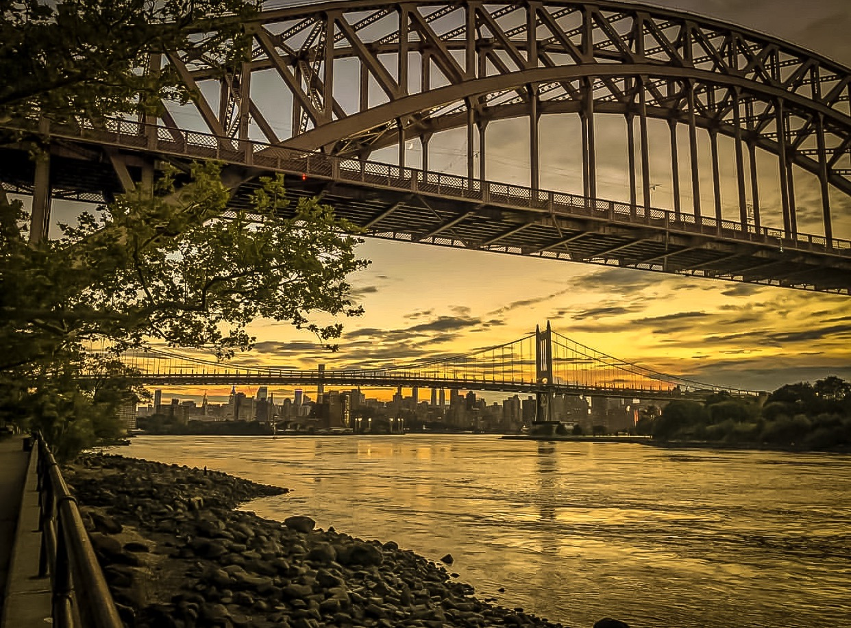 that moment when the sunrise turns clouds into small pieces of art in the skies. from astoria park, east river, looking at the hells gate bridge and triboro bridge.