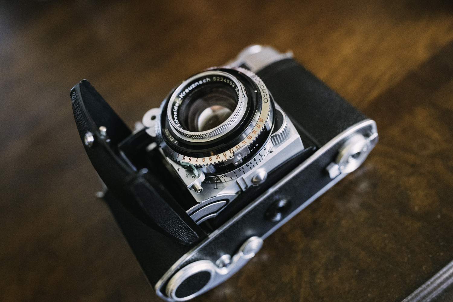 Notice the EV selector under the lens. This is indicated by the numbers 2-18. We also see the knob that is used to help turn the lens for focus. The camera can only be folded when focus is set to infinity.