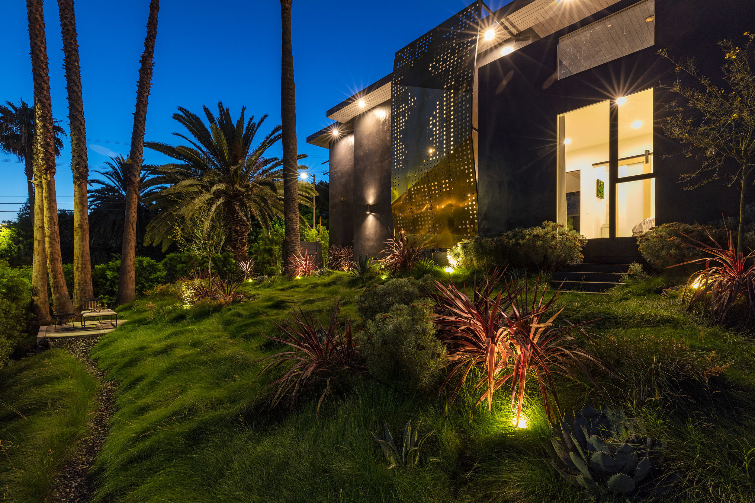 Great Outdoors - ·ART is landscape is art·Brass Façade·Geometric Green Wall·saltwater pool·Drought-tolerant gardens·5 DISTINCT OUTDOOR AreasThis residence is a case study for indoor-outdoor living. Landscape as art; Art as landscape. Outdoors, the 9,700-square-foot lot includes five various but connected seating areas completed by meadows of fescue grass and gorgeous drought-tolerant gardens. Sunlight intentionally bounces off a 21-foot-tall perforated brass façade at the main entrance; a tranquil saltwater pool is flanked by a 36-foot-long abstract green wall. Upstairs, patios boast wall cut-outs that poetically frame sections of the sky. A rich, varied textured palette throughout sports subdued colours and artisan-crafted details as a symbolic nod to the five elements (even referenced in the names of plants such as