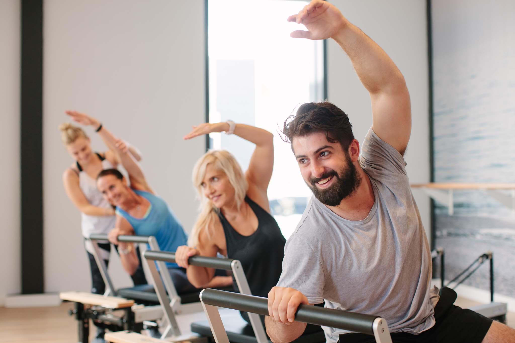 man smiles in reformer pilates class.jpg
