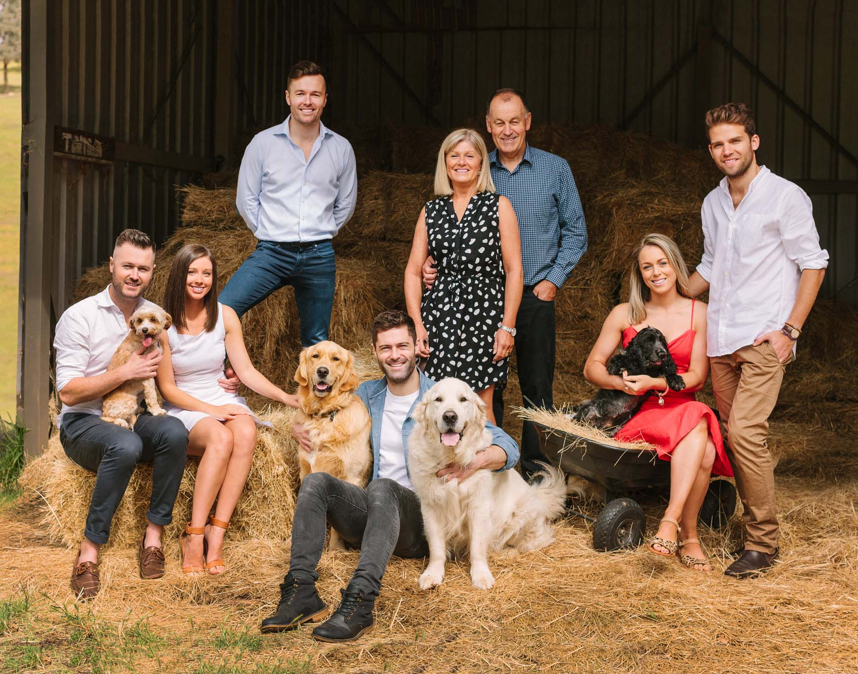 Family photo in a barn with dogs