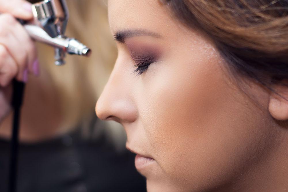 Make-up Artist mit Airbrush Pistole und Model