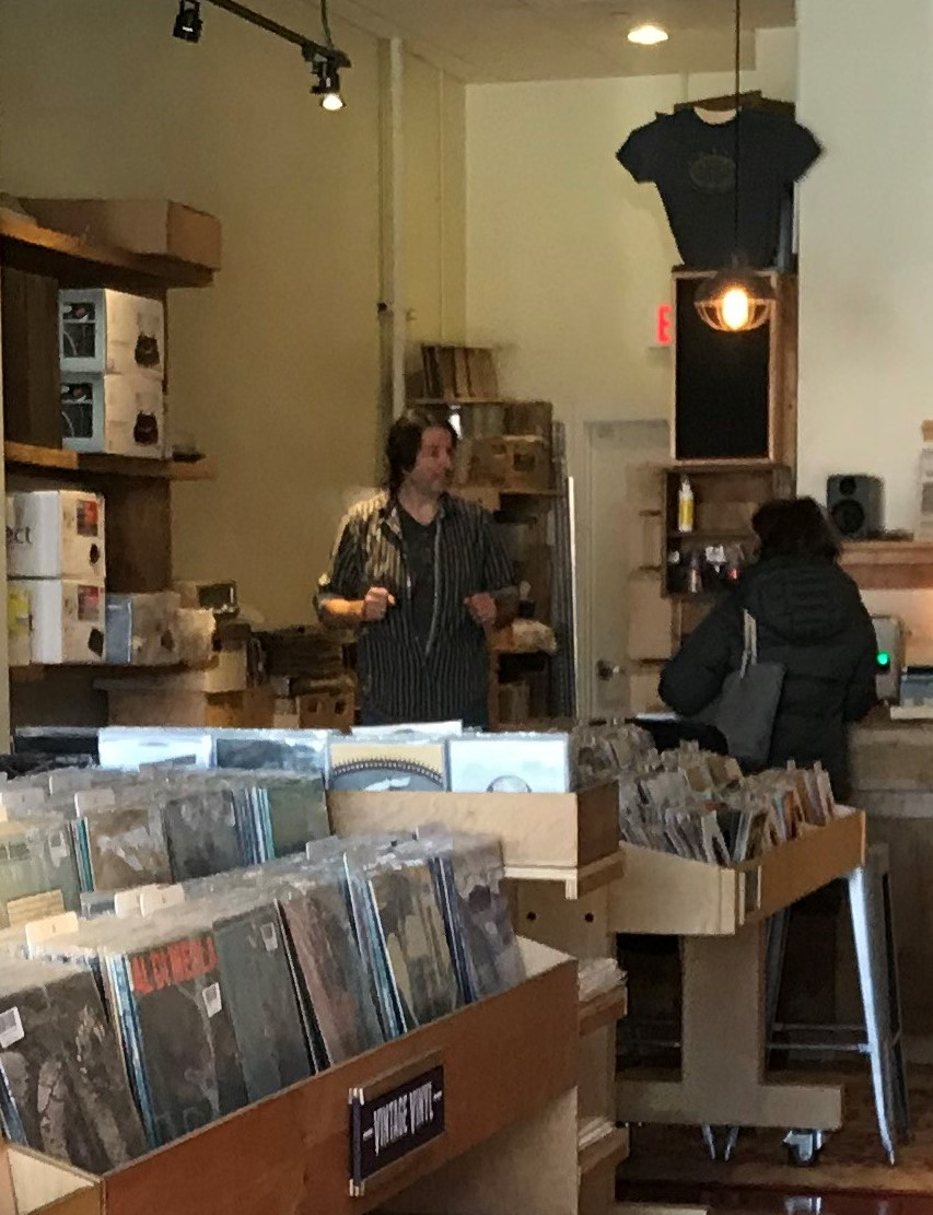 Mile Long Records owner Michael Paeth talks to a customer at his store in downtown Wheaton