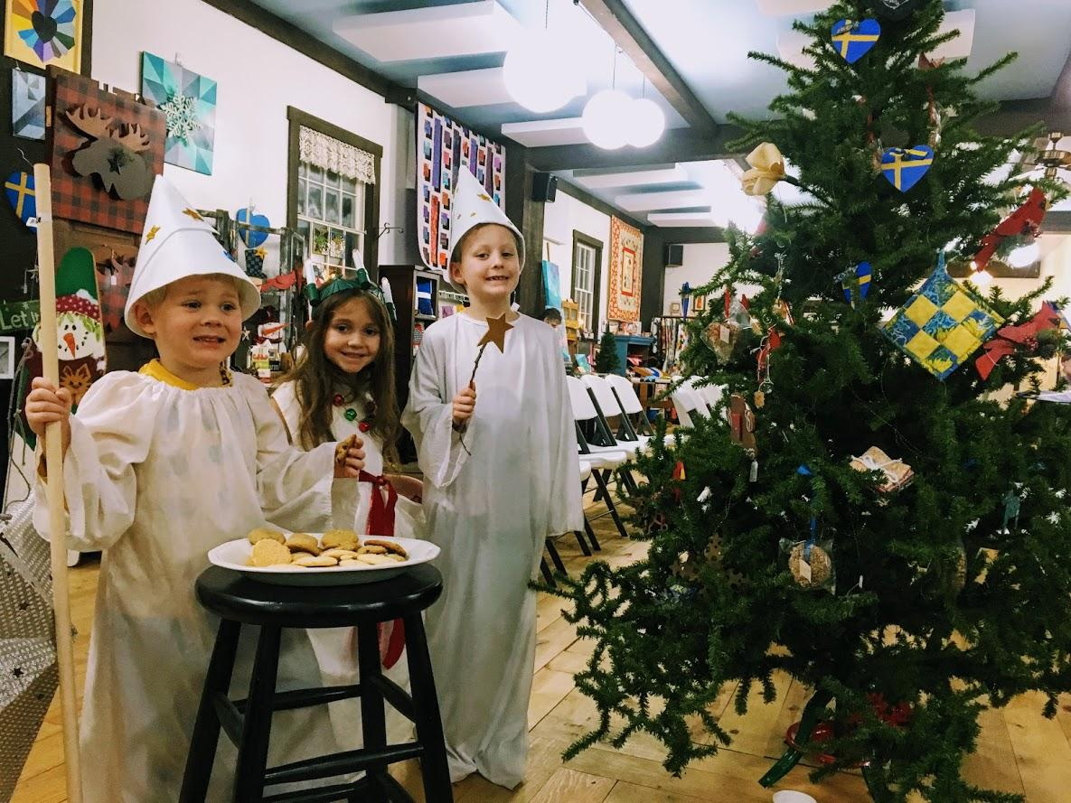 Three children dressed as Star Boys and a Lucia Girl welcome guests to the Creative Commons in Bishop Hill (photo courtesy of WIUM)
