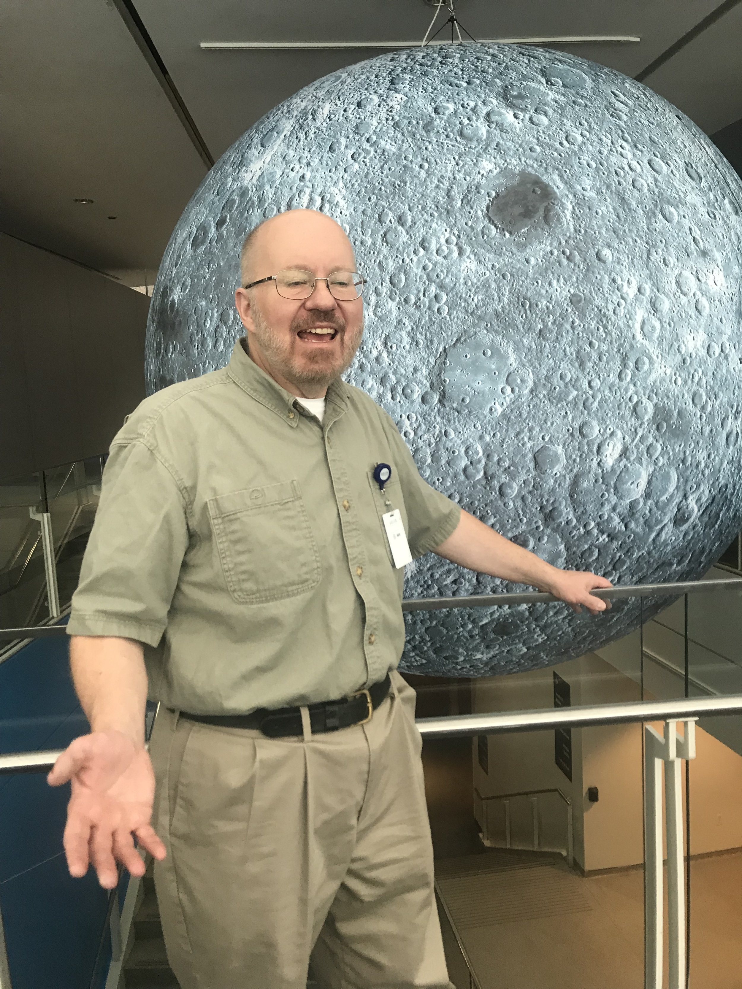 Astronomer Mark Hammergren stands in front of a new moon globe at the Adler Planetarium. This view gives visitors a look at the far side of the moon.