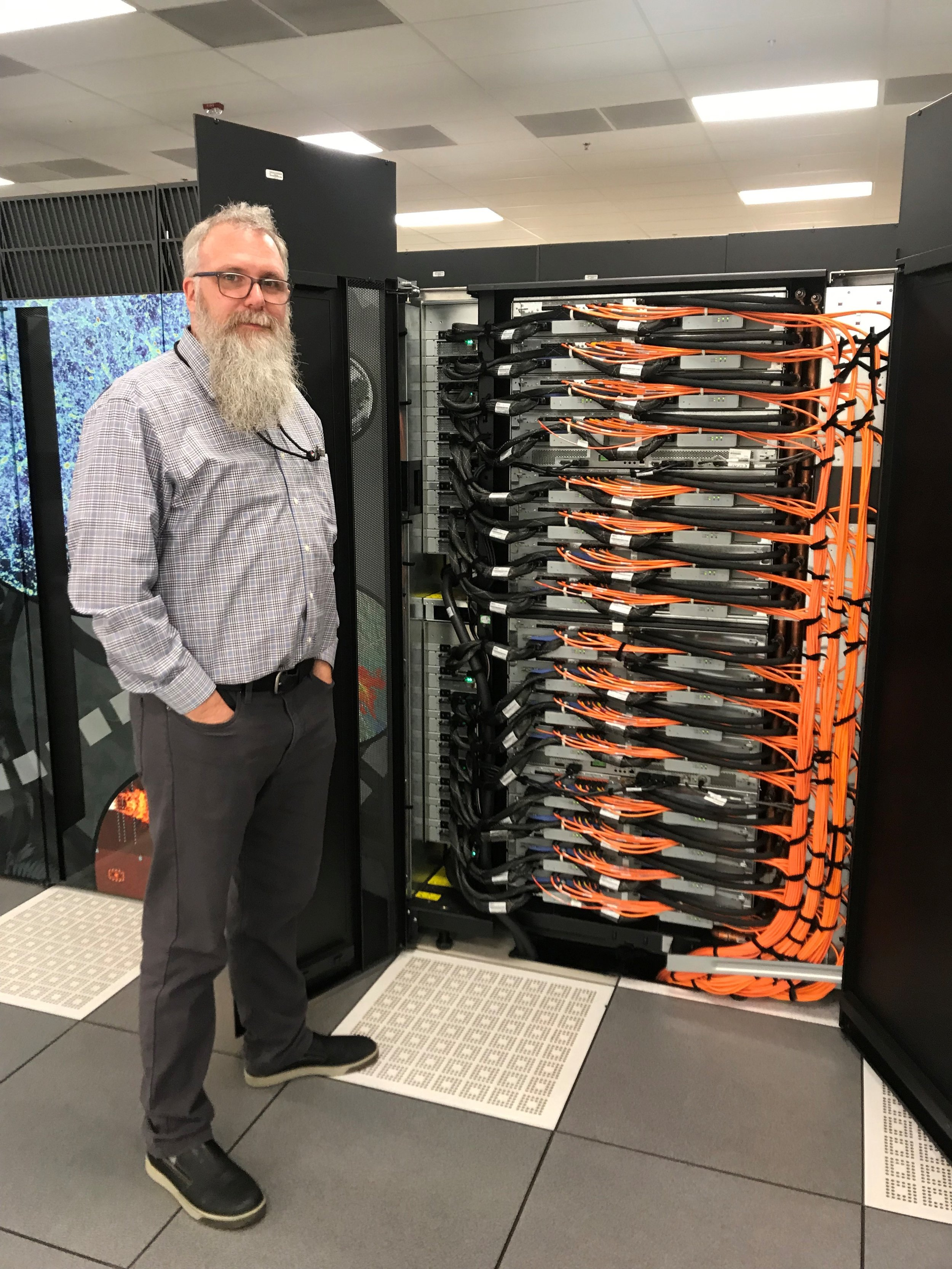 Michael Papka , the Division Director for the Argonne Leadership Computing Facility, standing in front of one of the Mira super-computer cabinets. The 48 computer cabinets each weigh two tons