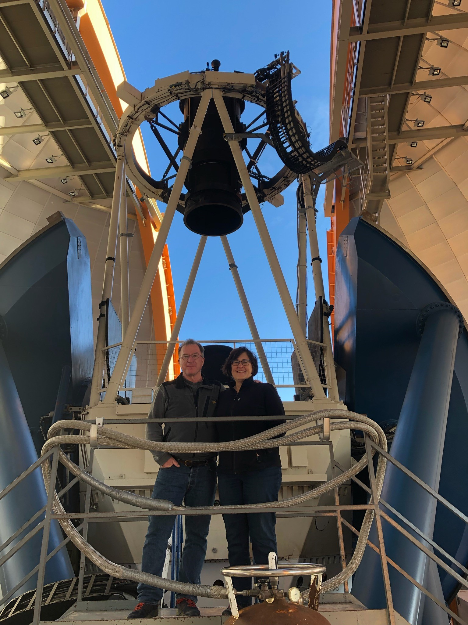 Brenna and Tom standing with the Dark Energy Camera in Chile