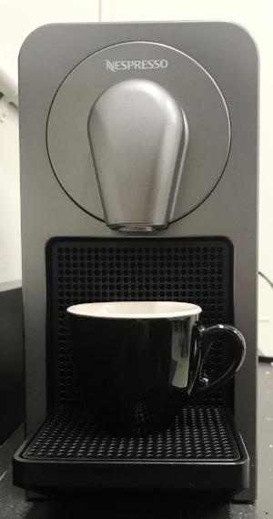 Nespresso Prodigio and a ceramic espresso mug.
