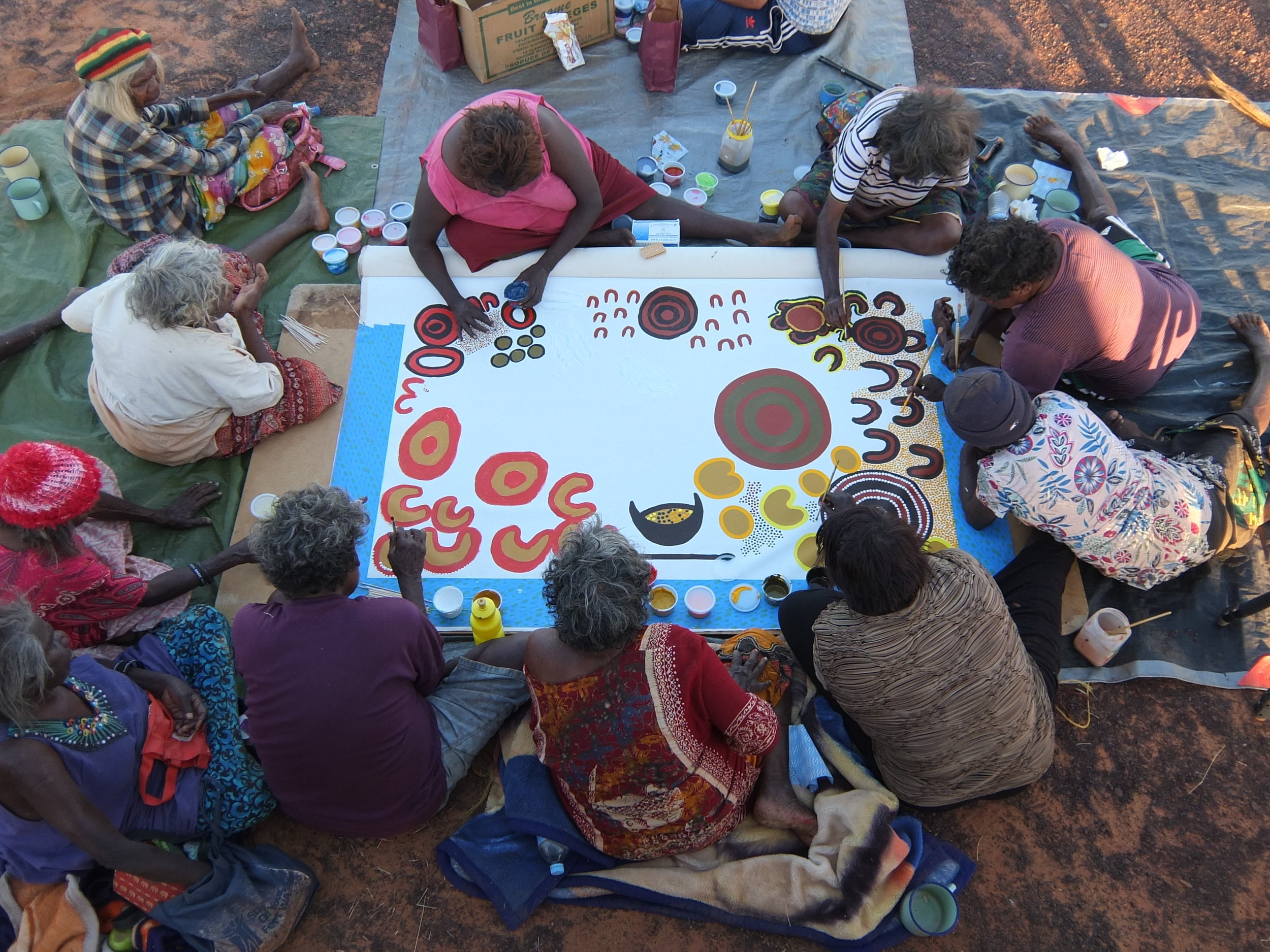 Overview shot of women painting during the  Tjawa Tjawa  film shoot