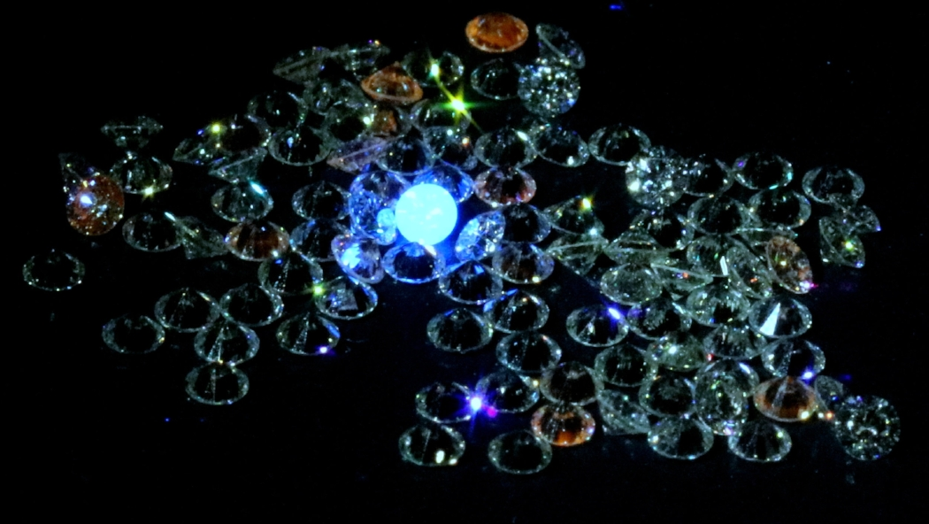 mined diamonds glow blue in a parcel of lab grown diamonds