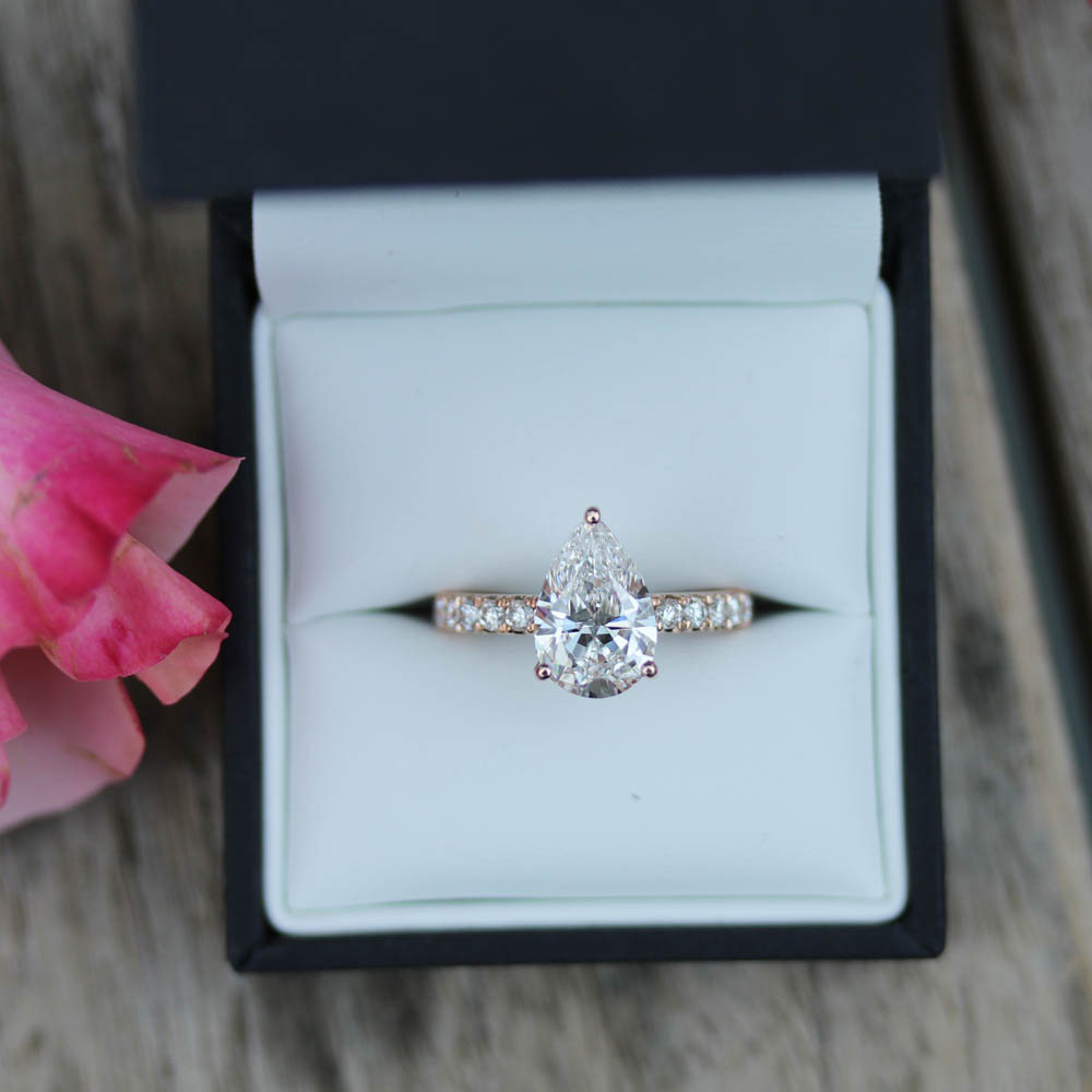 three prong pear cut lab diamond engagement ring with diamonds down the band in rose gold setting