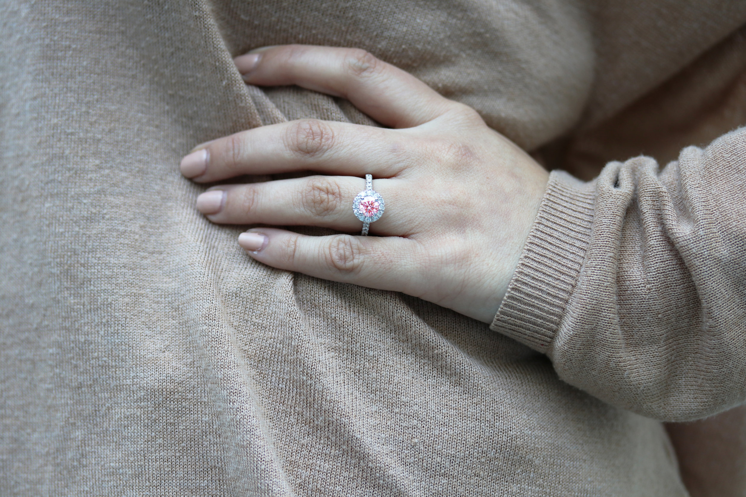 fancy pink lab diamond engagement ring with diamond halo and diamonds down the shank