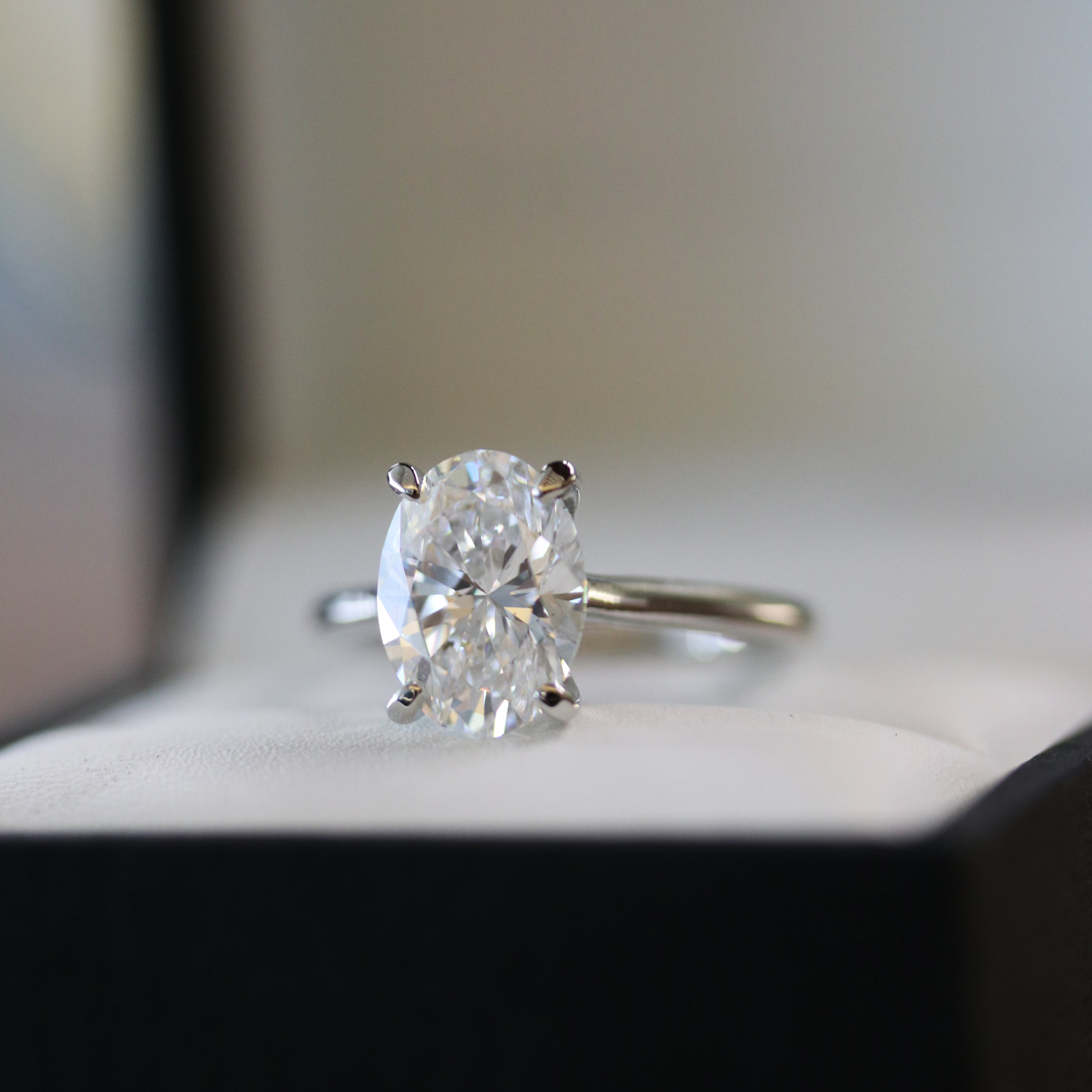 Oval diamond solitaire engagement ring in four prong platinum setting