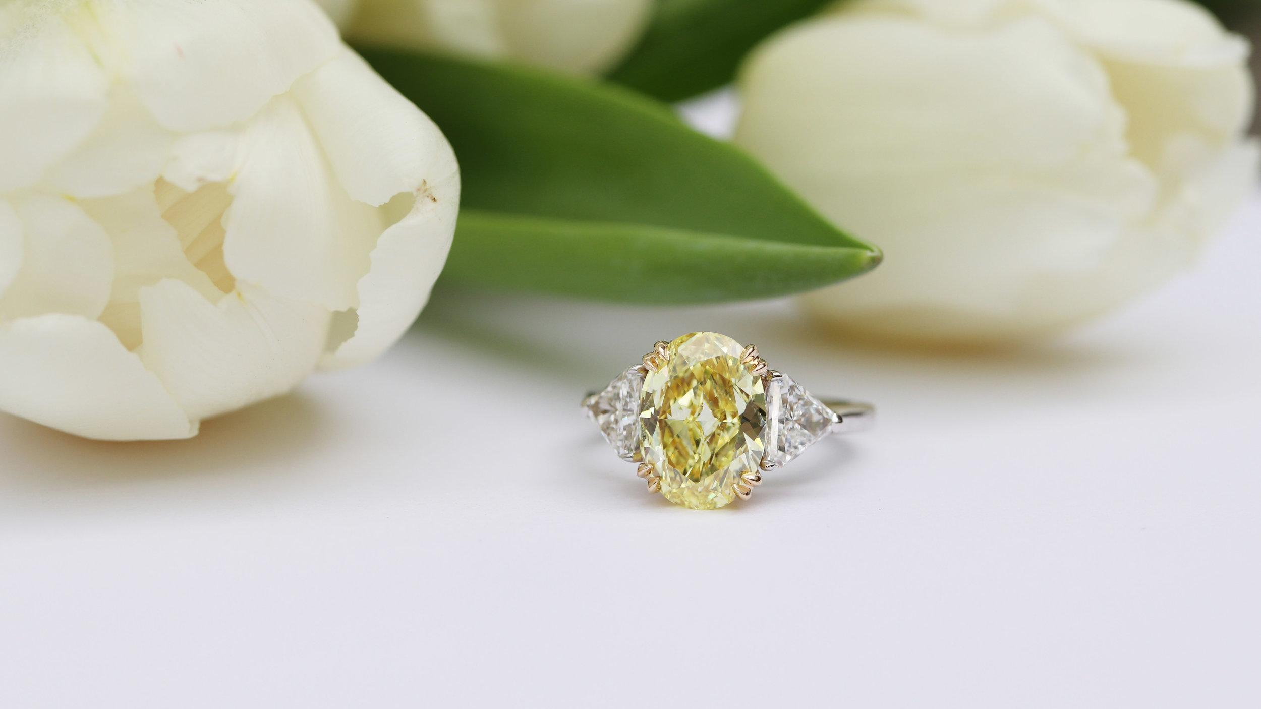 Fancy light yellow lab grown oval cut diamond engagement ring with three sided diamond band Ada Diamonds