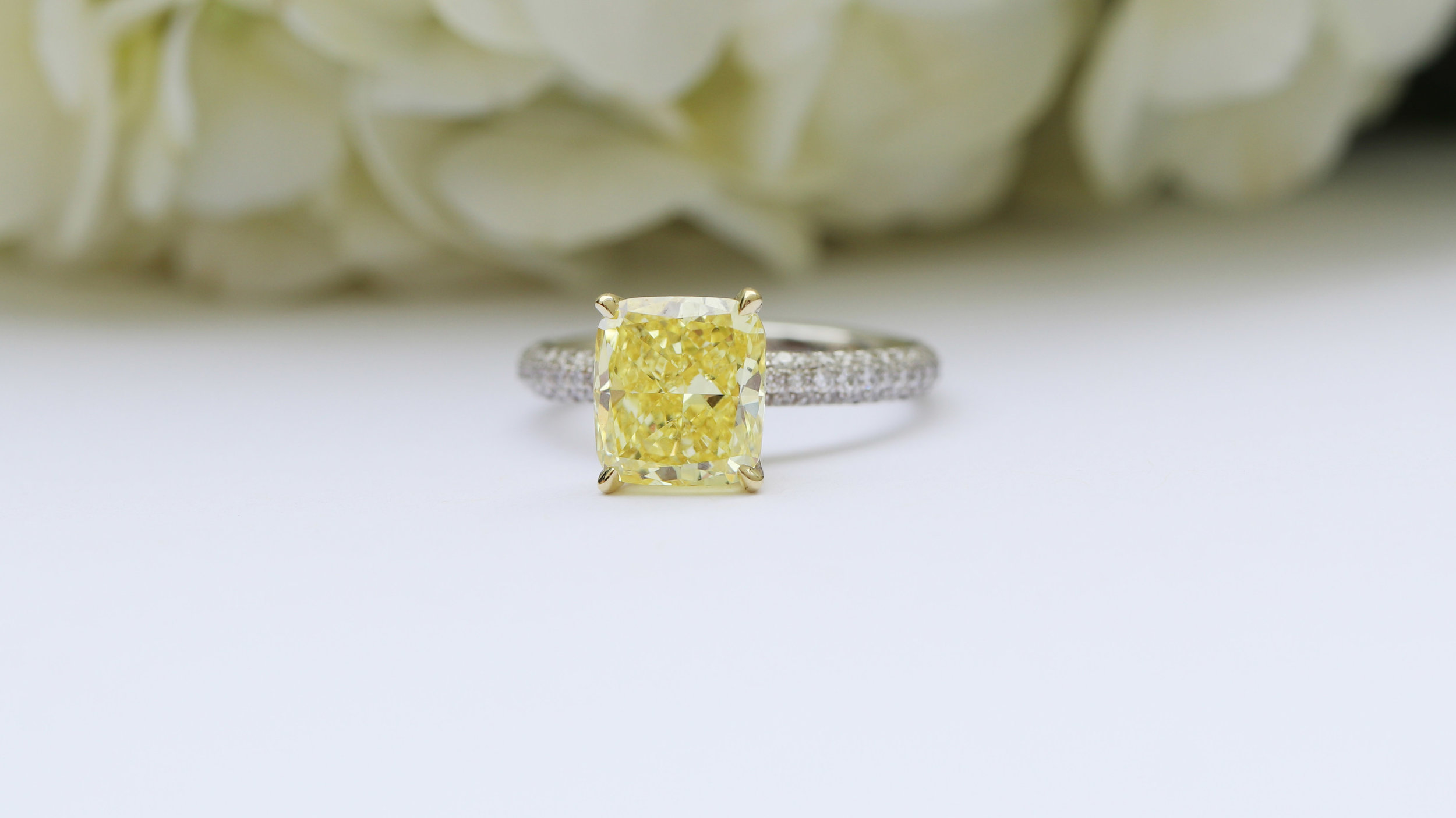 Custom lab diamond engagement ring with fancy yellow radiant lab grown diamond center stone and a white diamond band