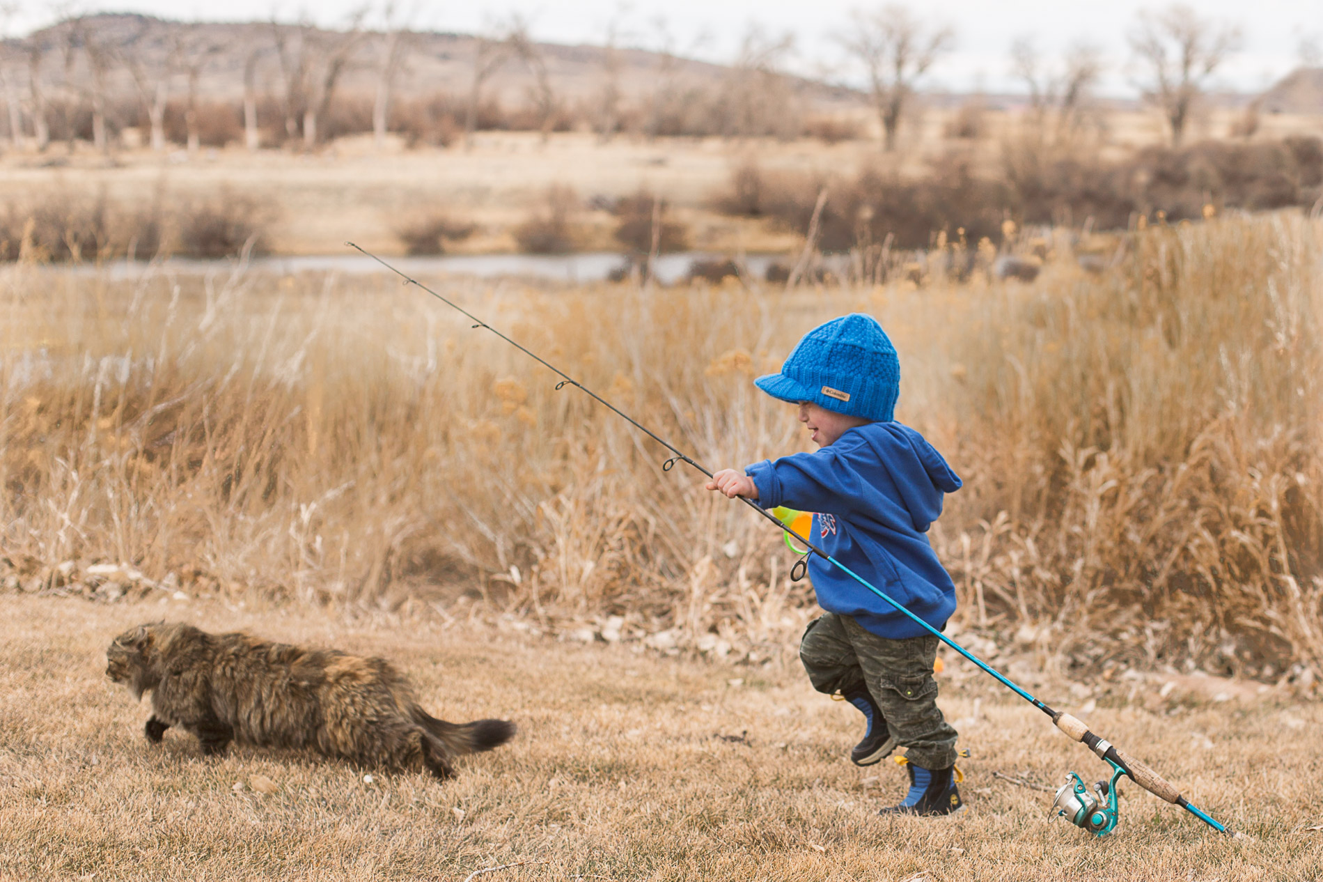 boy toddler and cat going fishing outdoors in wyoming