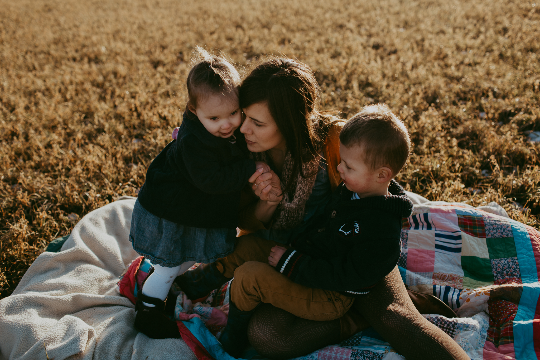 Mom with children on blanket in field