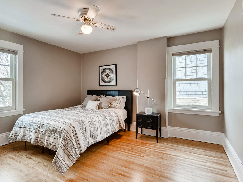 Paring down your furniture to just the essentials, like the bed and nightstand here, helps a home feel bigger and brighter. If practical, remove window coverings to bring in the most light.