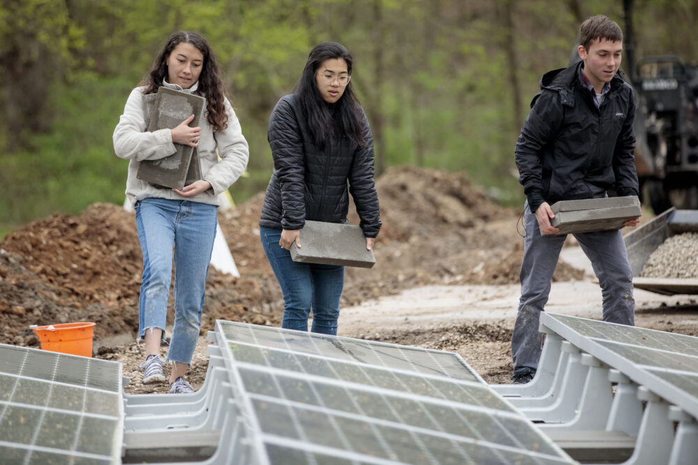 Coyle (left), Chen and Cepeda install solar panels at Tyson Research Center. (Photo: Whitney Curtis/Washington University)