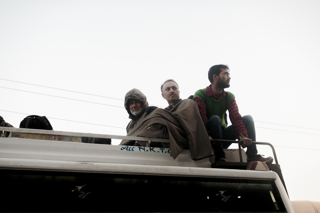 Three men on the roof of a bus, Srinagar, India