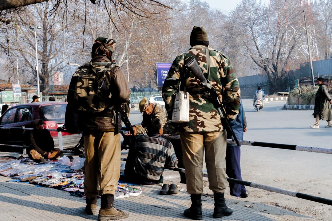 Three soldiers ask a merchandiser in the street, Srinagar, India