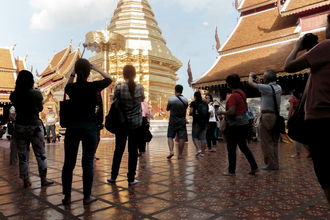 Tourists taking pictures of a temple, Chiang Mai, Thailand
