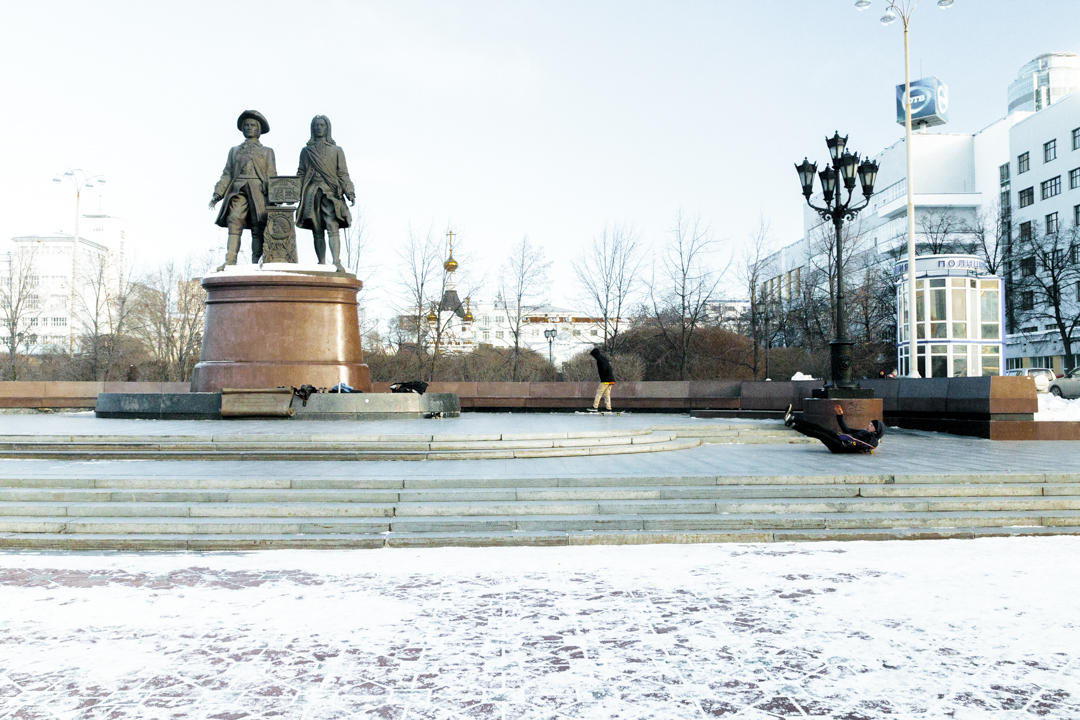 A young man tumble from his skateboard in front of a statue, Iekatrinbourg, Russia