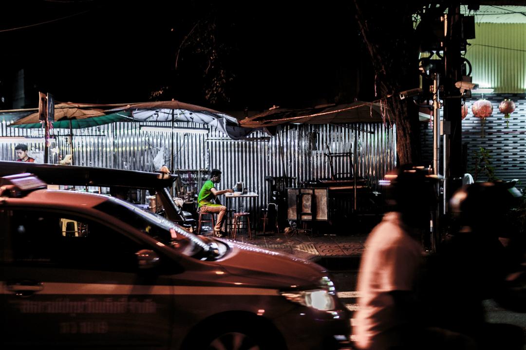 A man eats in the street, Bangkok, Thailand