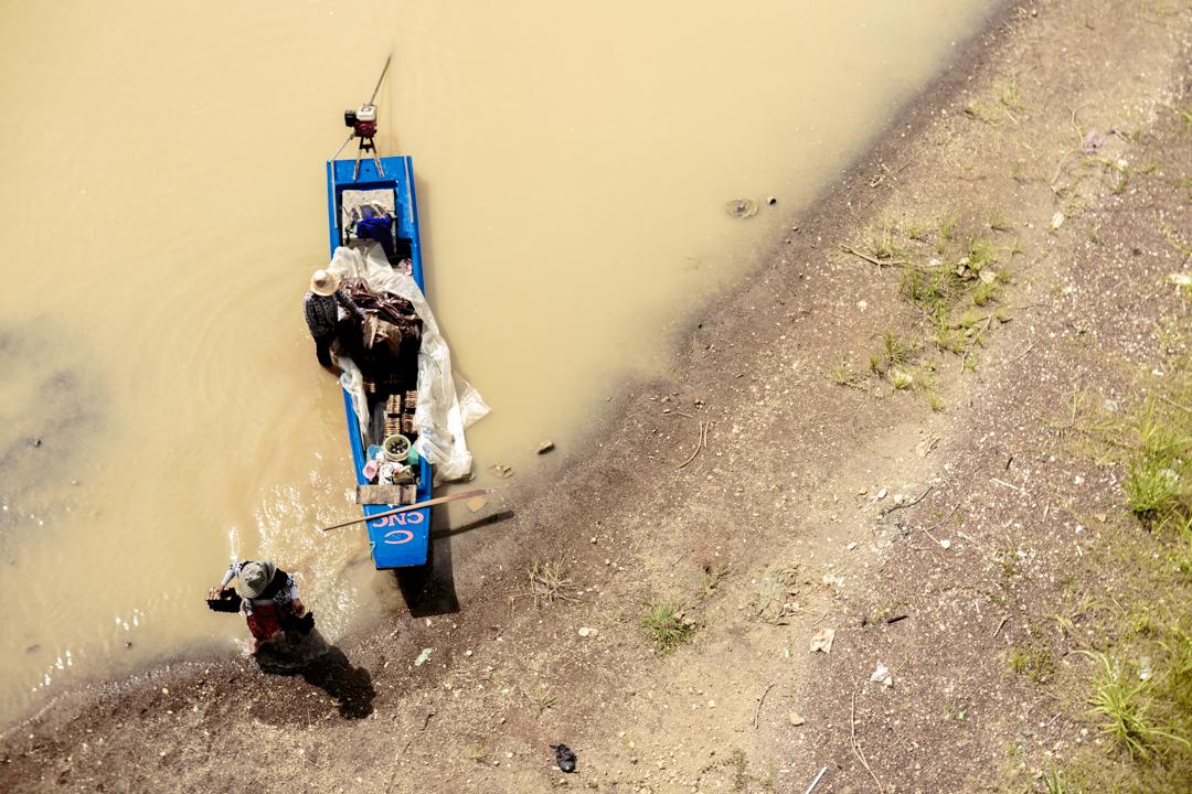 A man and a woman discharge a boat, Battambang, Cambodia