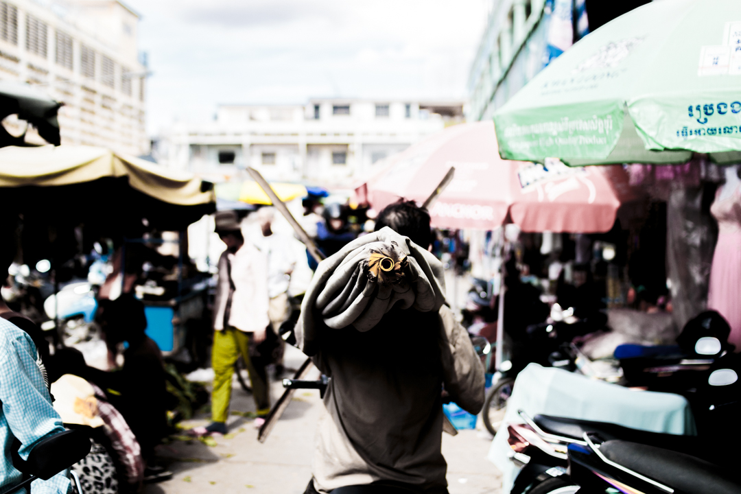 A man walks towards a market with a n umbrella, Battambang, Cambodia