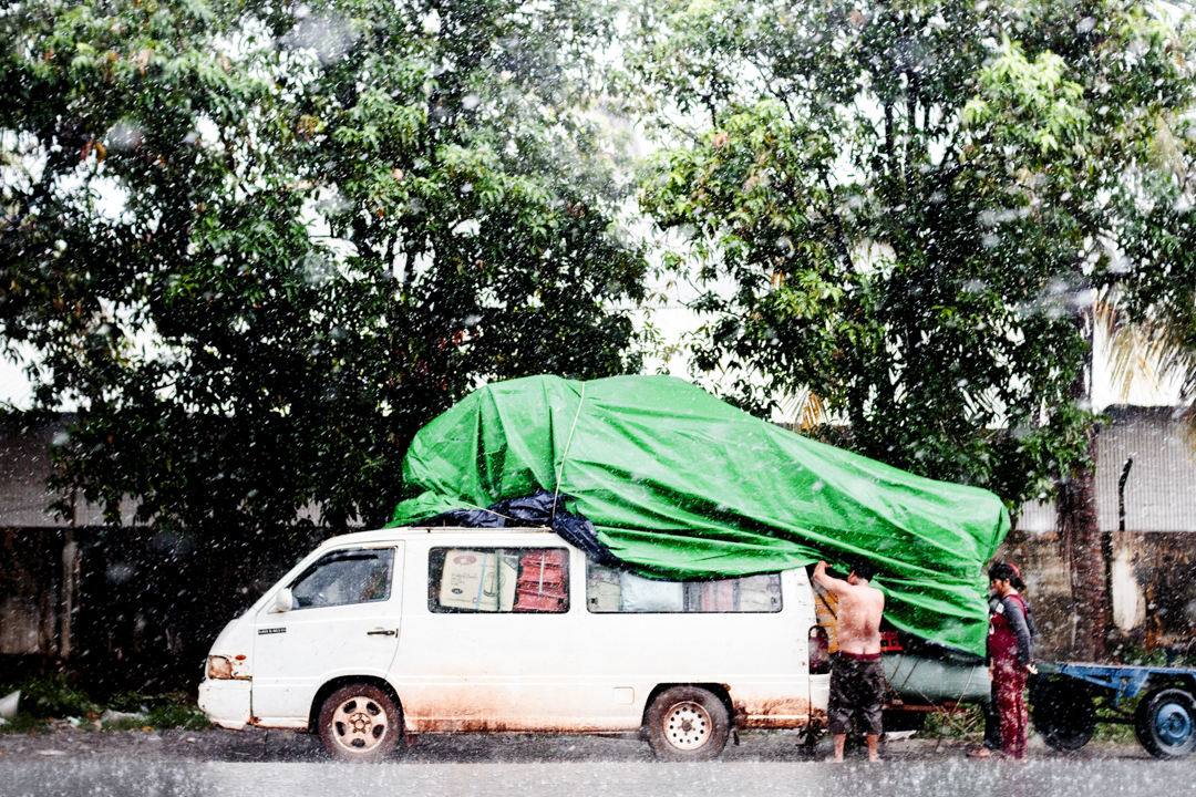 Two people put a tarpaulin on a truck as it start to rain, Phnom Penh, Cambodia