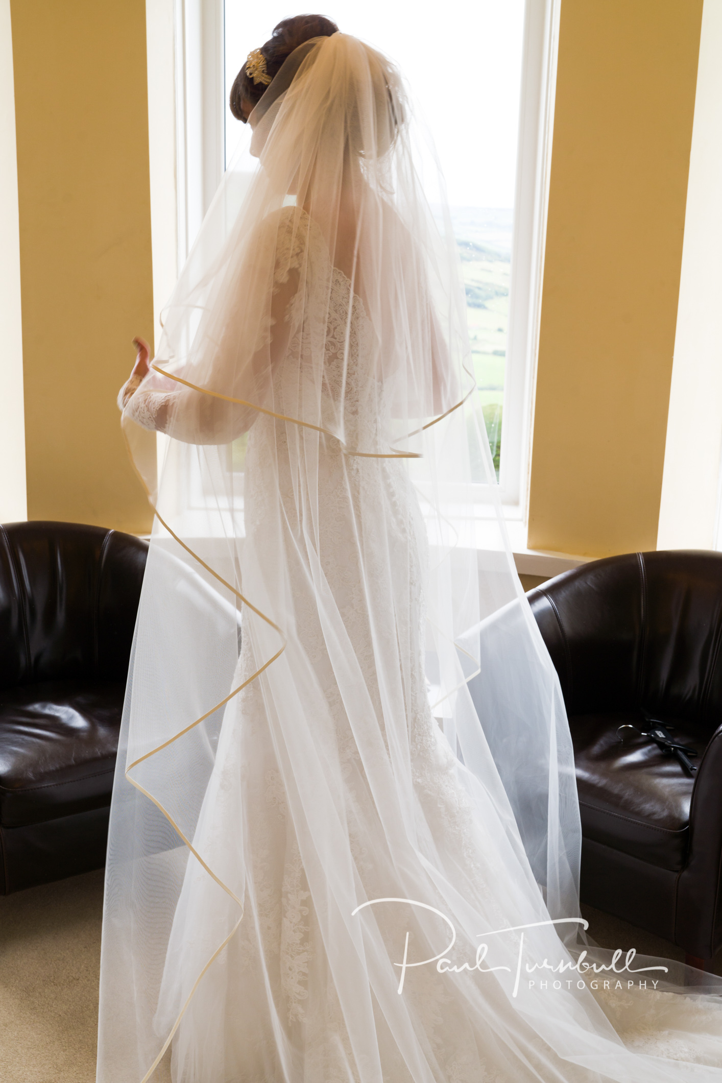Bride getting to grips with the dress at Raven Hall, Ravenscar