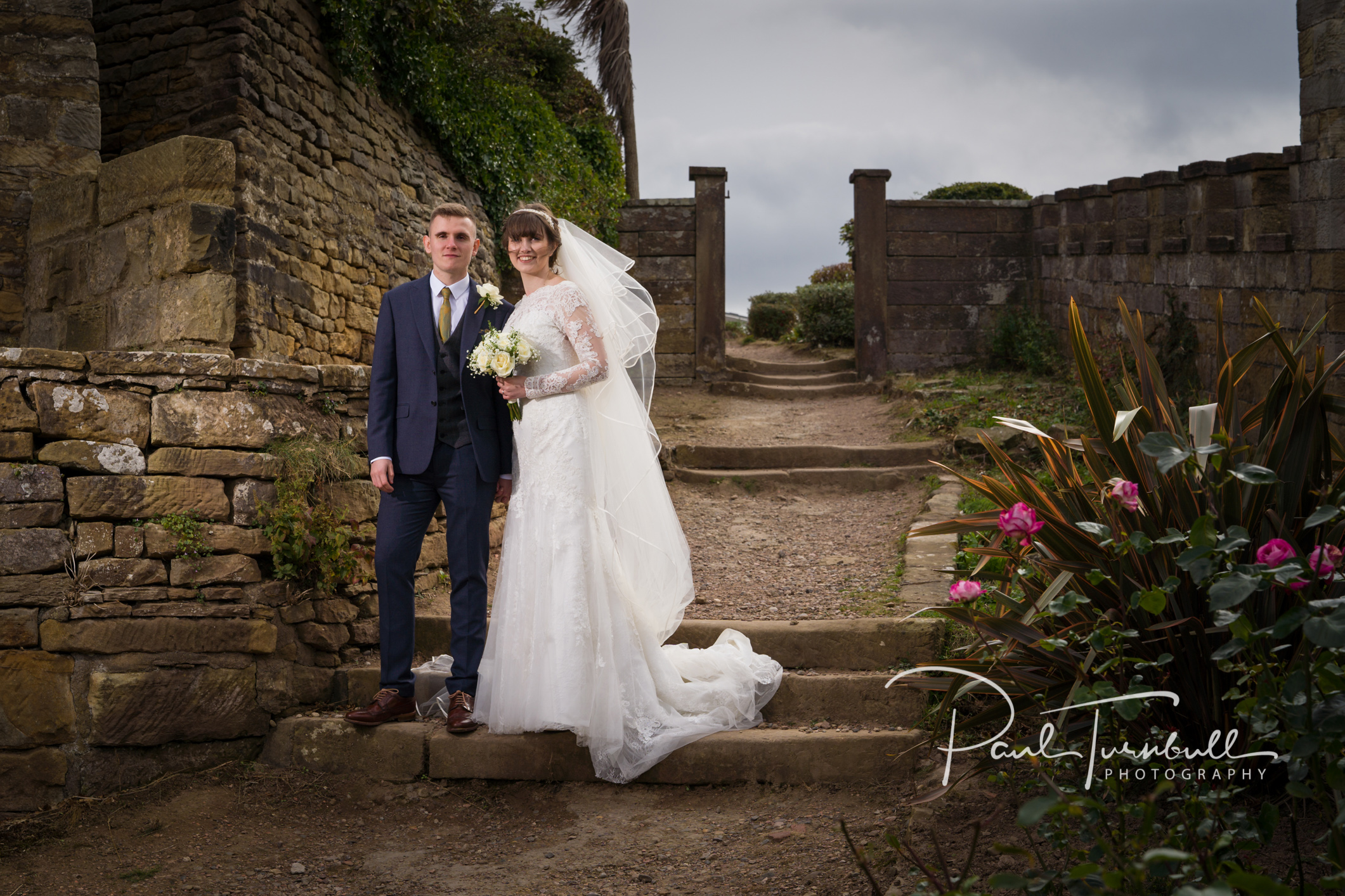 Bride and groom in the gardens of Raven Hall after their wedding