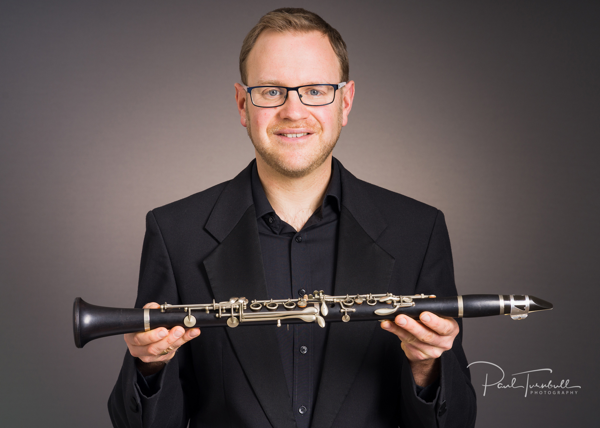 Professional musician and music teacher Jonathan Sage holding his clarinet