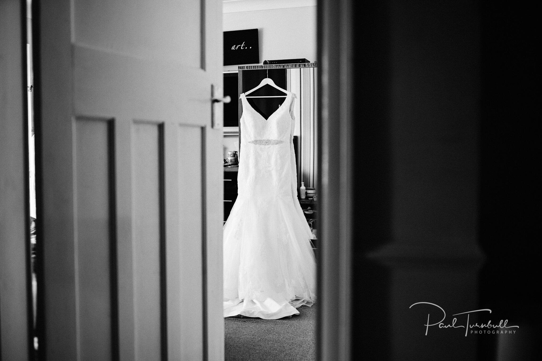 Wedding dress on hanger in bedroom. Wedding Photographer Hull