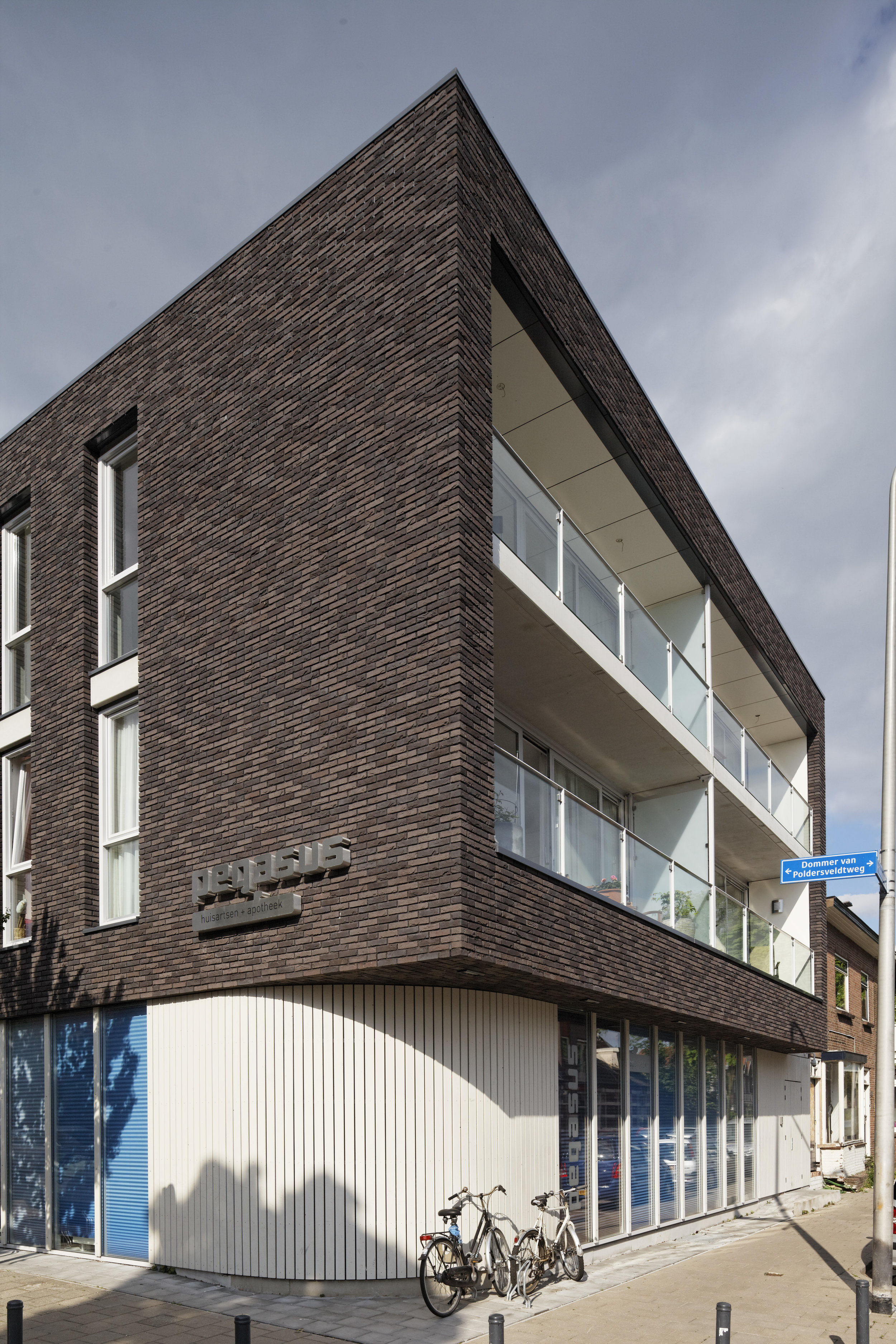 the volumes housing the apartments are clad with dark brick, accentuating the private character