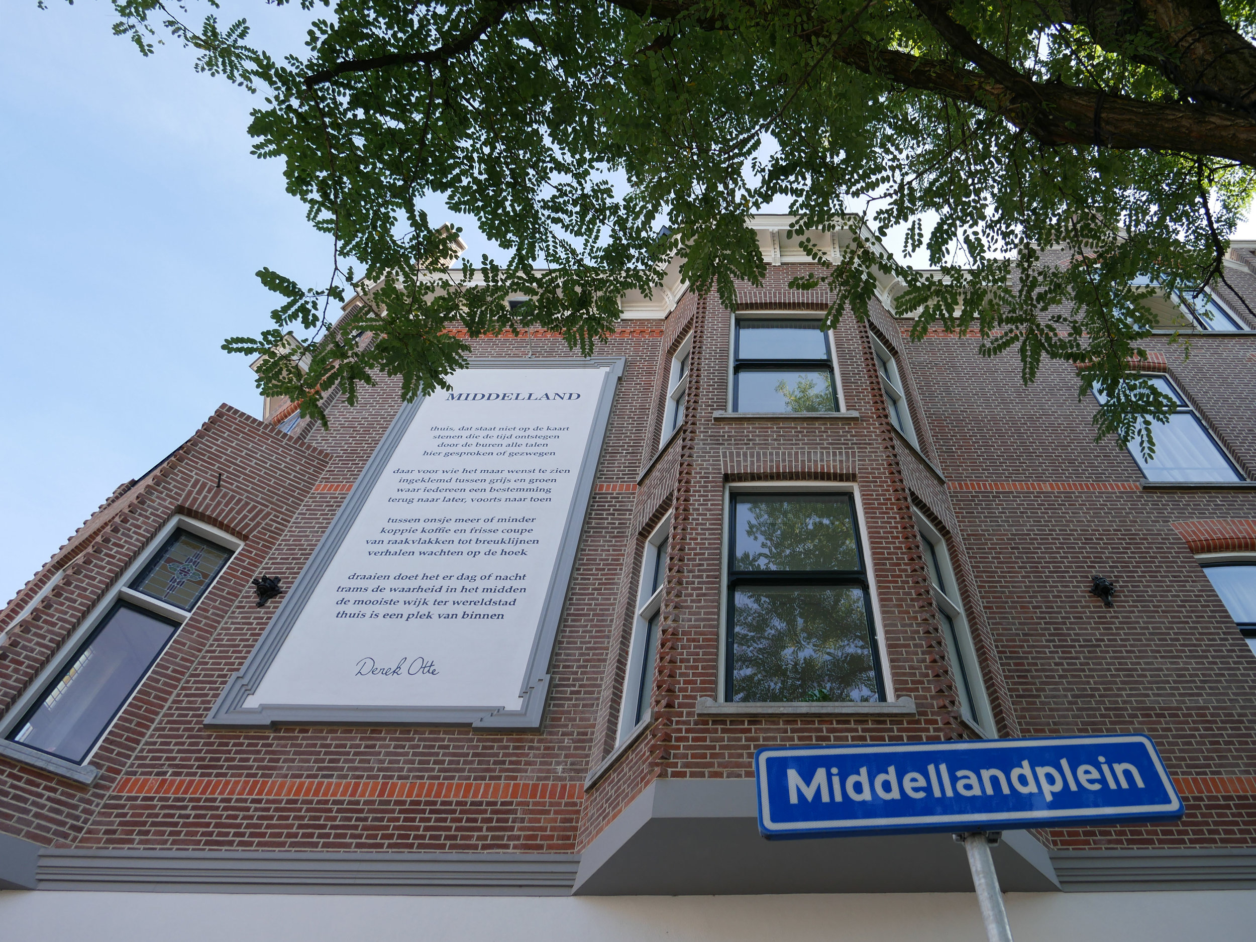 looking up to the restored brickwork facade with the classical advertisement frame ànd a poem by Derek Otte