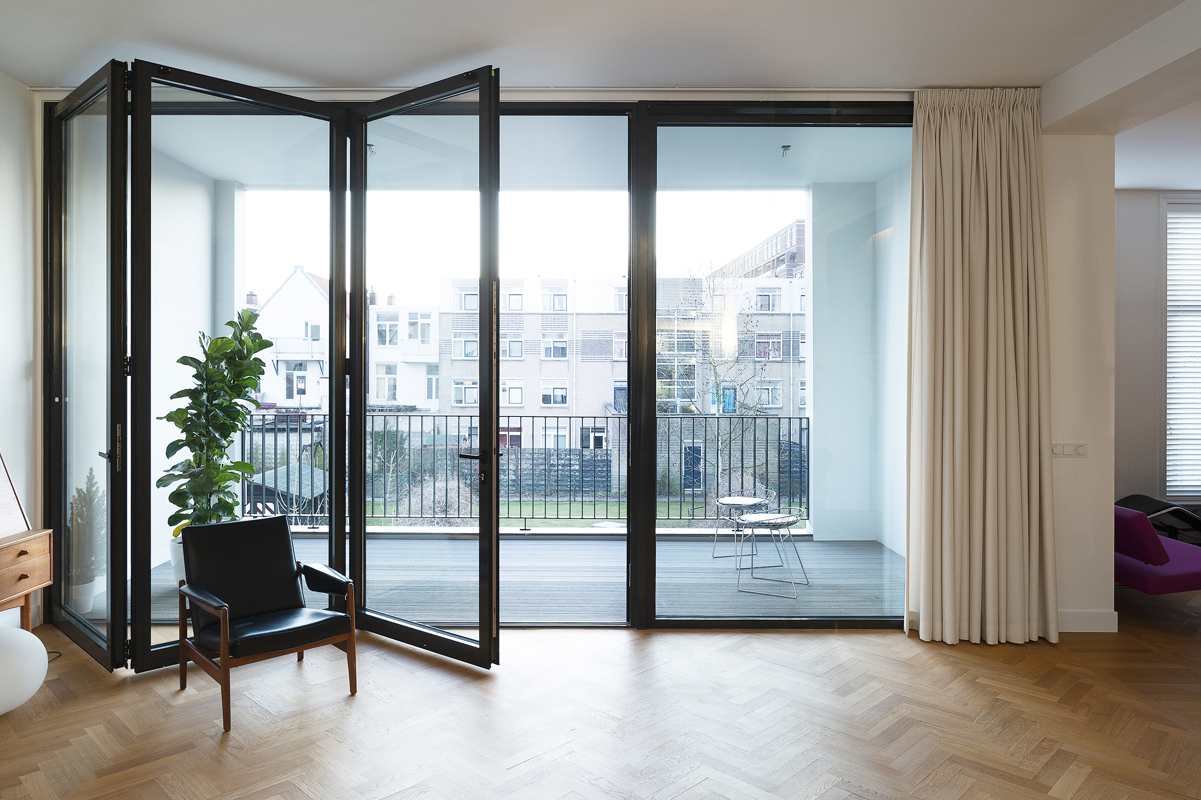 the large sliding doors connect the living room with the french balcony