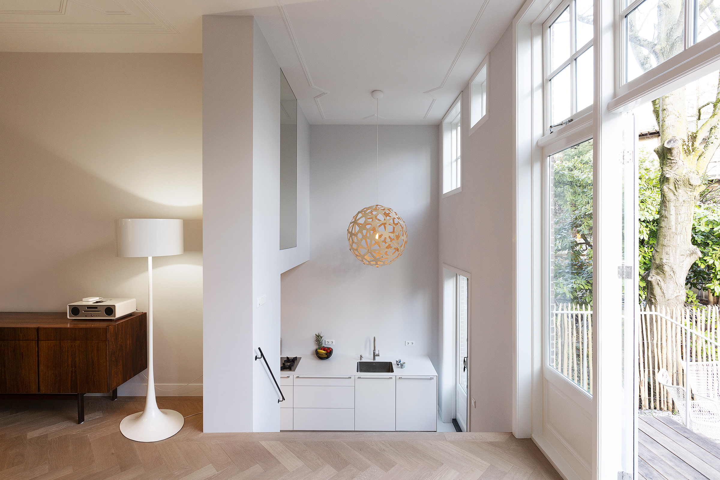 By sacrificing a part of the mezzanine and making a large opening in the dividing wall the kitchen becomes part of the living area. A wide staircase completes the intervention