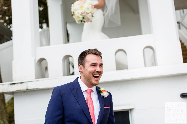groom laughs with bride behind