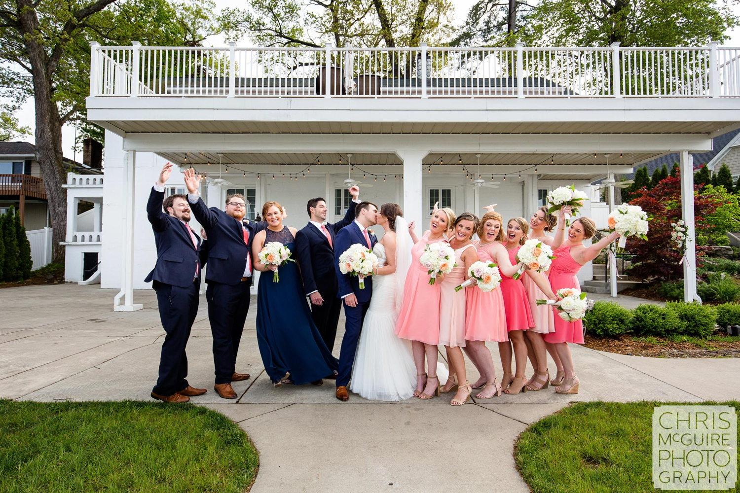 wedding party cheers as couple kisses