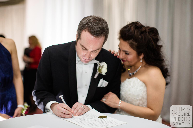 bride groom signing marriage license