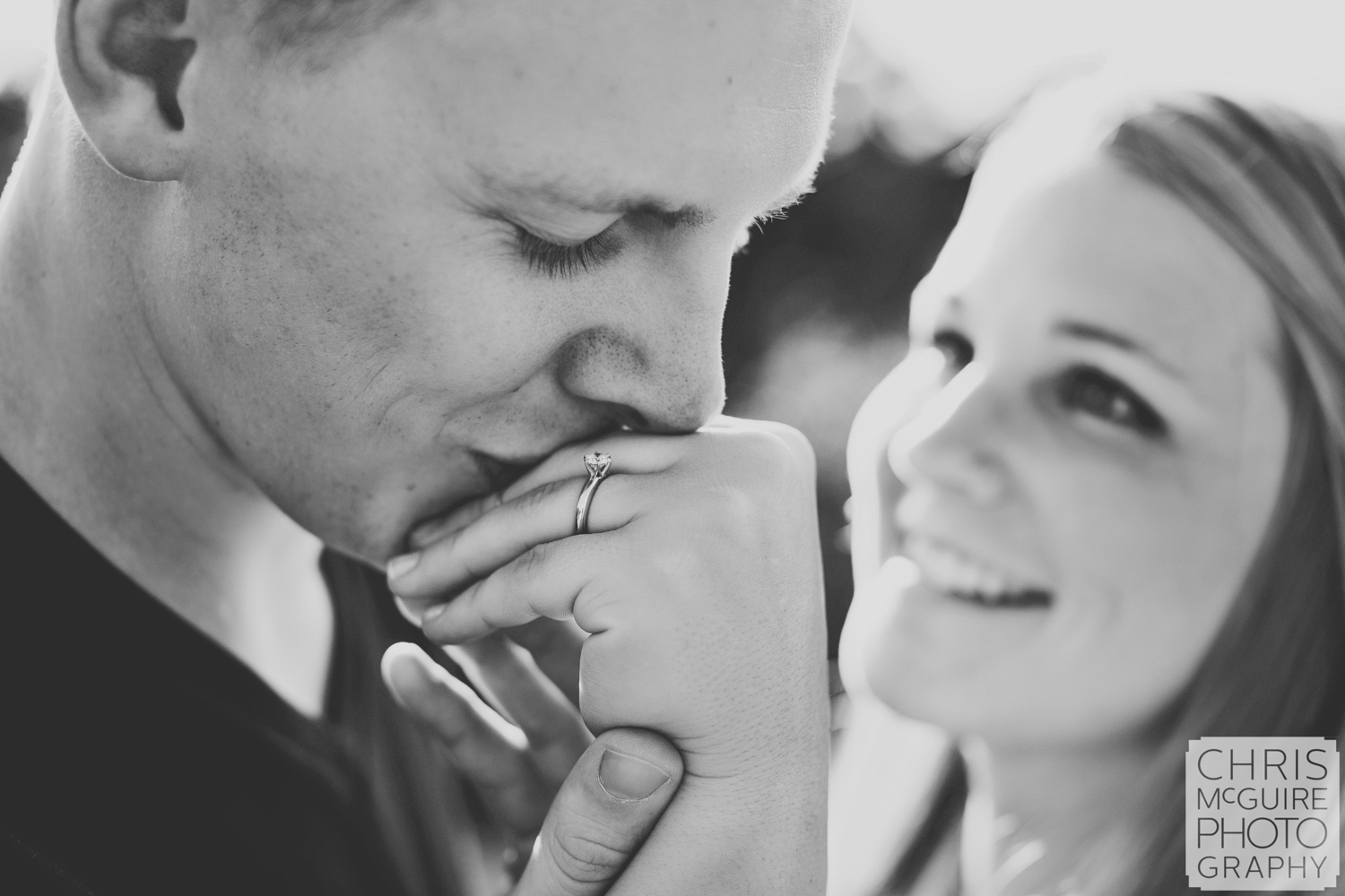 man kissing womans hand engagement ring